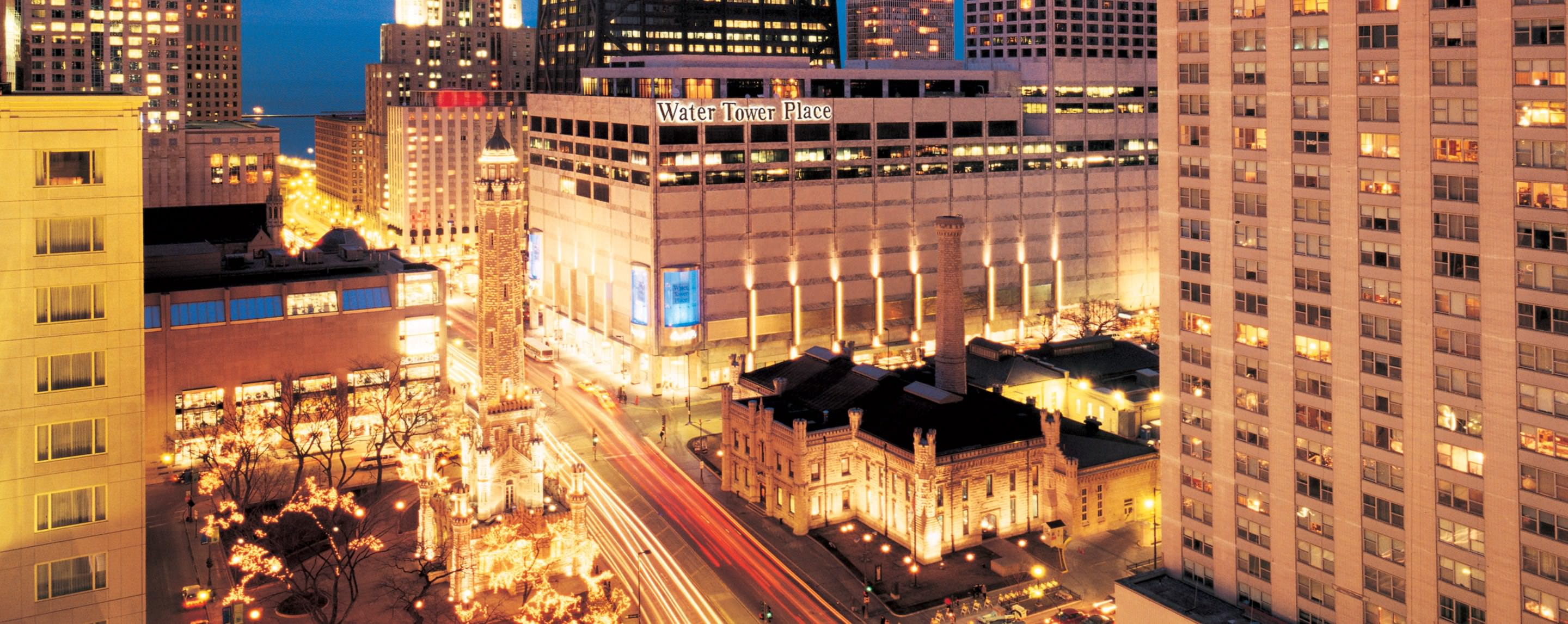At night, an aerial view shows Water Tower Place brightly lit in downtown Chicago.