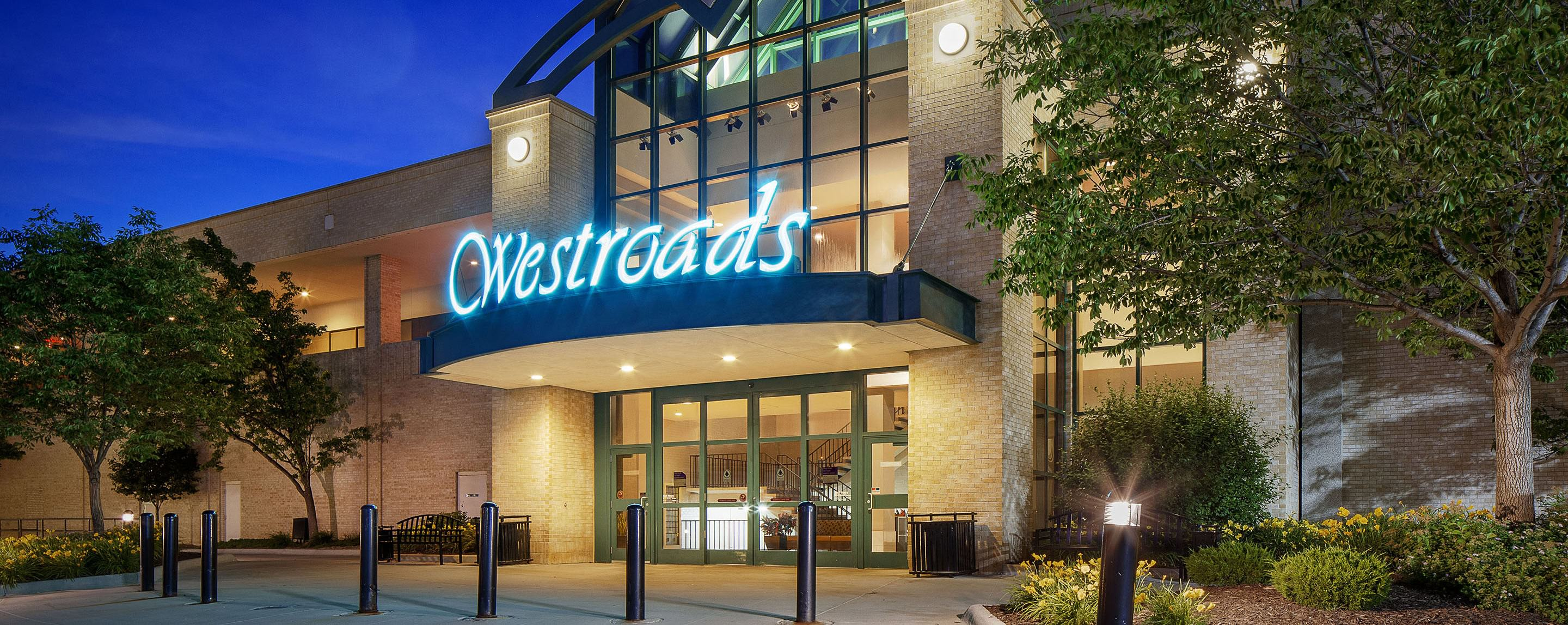 At night, the Westroads Mall sign is brightly lit illuminating the entrance to the mall and surrounding landscape.