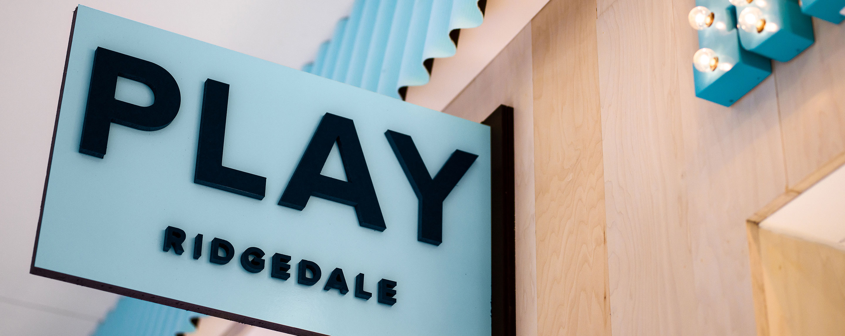 "An eggshell blue sign says ""Play Ridgedale"" in black letters in front of the Ridgedale Play center at Ridgedale Center in Minnetonka, MN."