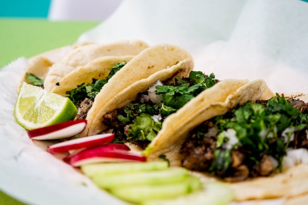Prepared tacos with lime, radish, and cucumber on the side