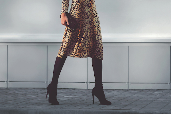 Women in leopard dress holding clutch