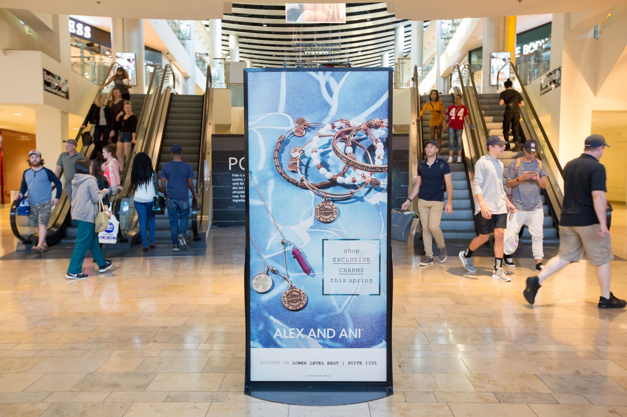 In a walkway next to a property's elevators, a standalone sign advertises Alex and Ani