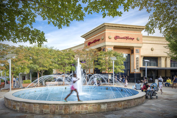 Girl walks along the fountain in front of The Cheesecake Factory