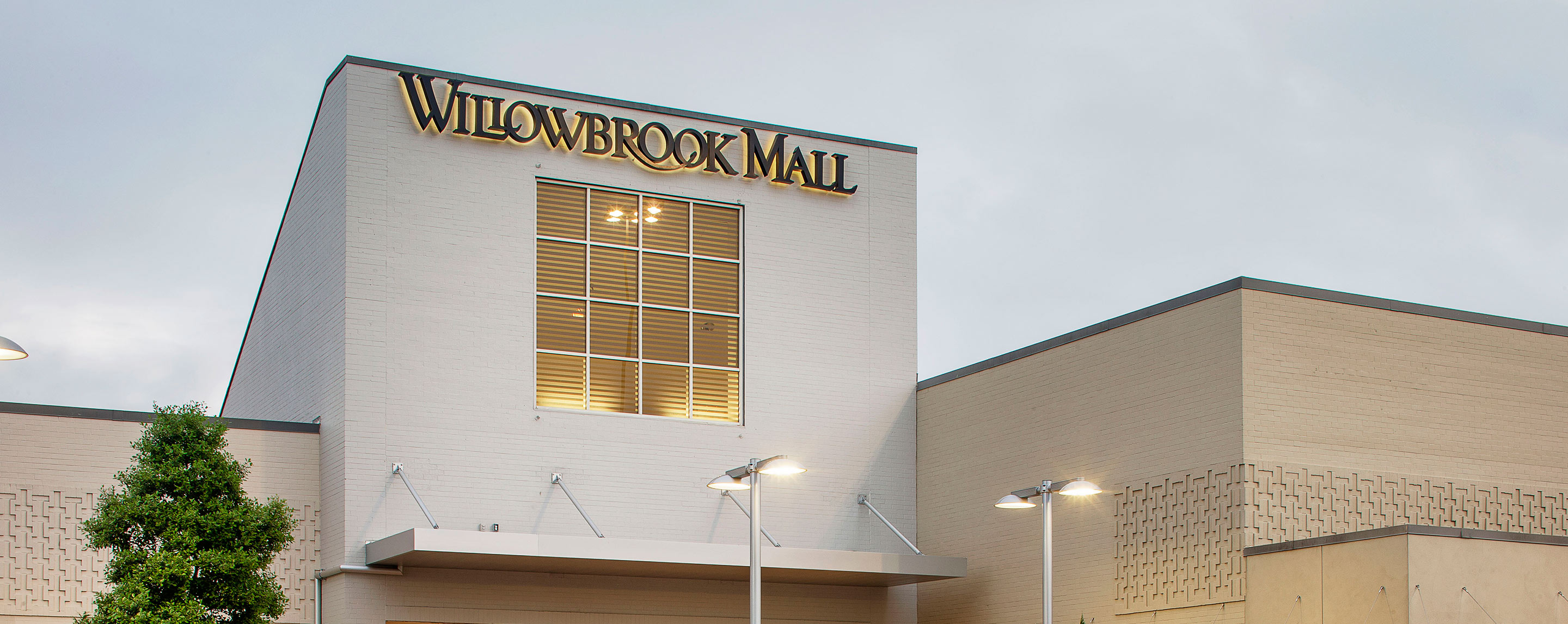 At dusk, the entrance to Willowbrook Mall is lit.