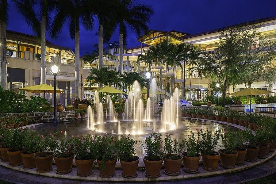 At night outside a property, a running fountain lights up and is surrounded by potted plants.