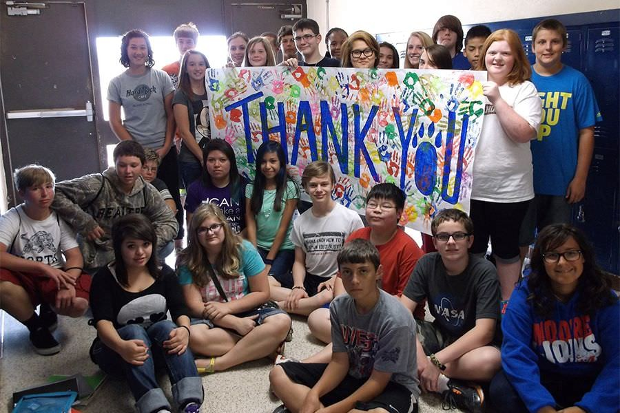 "A group of kids pose with a sign that says ""Thank You"" with their handprints."