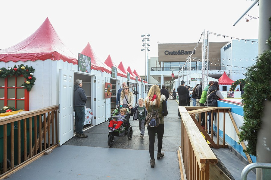 A family walks through the holiday market at Oakbrook Center. White tents line a festively decorated ice skating rink.