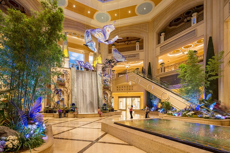 The interior atrium of Grand Canal Shoppes features a waterfall, a fountain, colorful indoor plants and big pastel butterflies hanging from the ceiling.