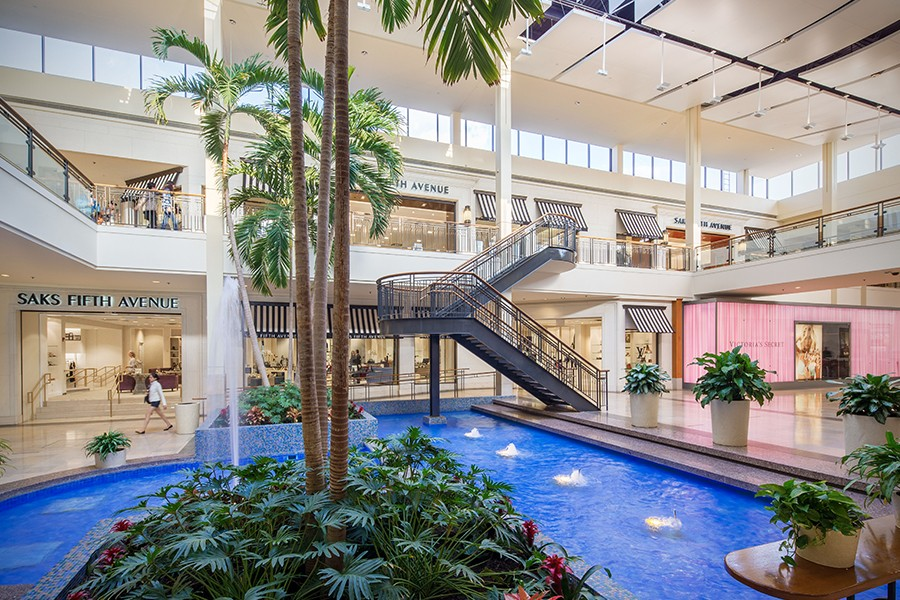 A decorative fountain surrounded by plants and palm trees at North Star Mall is enclosed by two levels of storefronts.