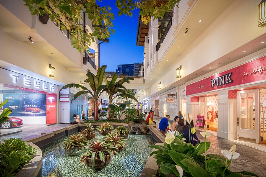 At dusk, visitors to Ala Moana sit by the fountain and stroll through an outdoor atrium lined with palm trees.