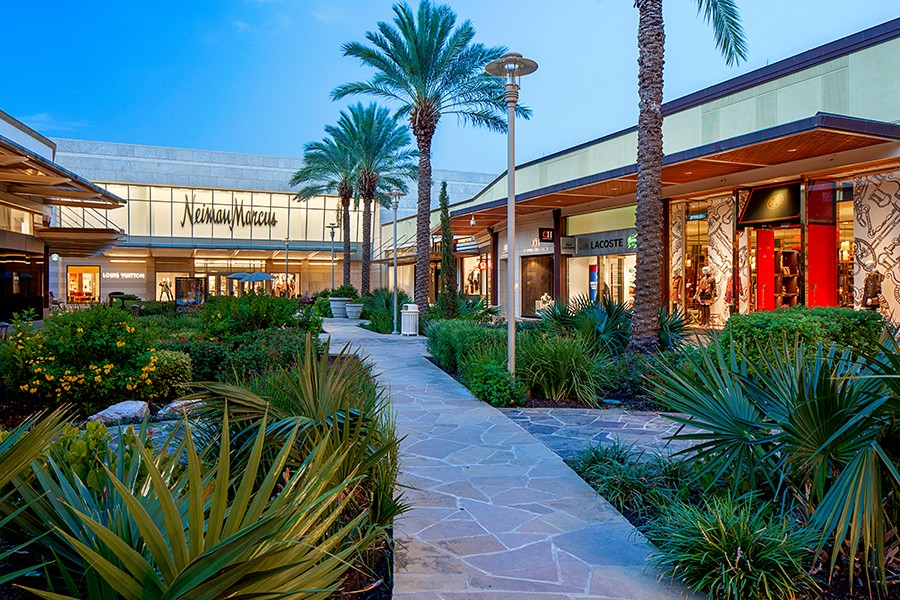 A Neiman Marcus storefront at The Shops at La Cantera is light up surrounding other storefronts and lush landscaping.